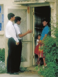 missionaries at door of home