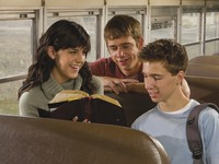 youth reading scriptures on school bus
