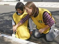 young women in yellow vests painting