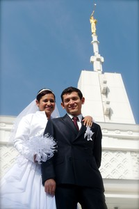 bride and groom with temple In background