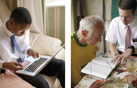 youth using a computer and missionary teaching a man