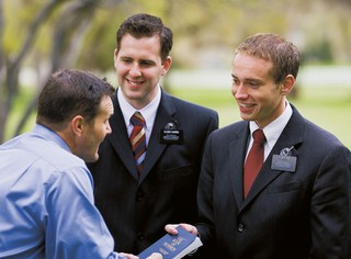 two elder missionaries giving man a Book of Mormon
