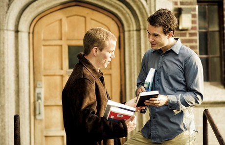 man handing Book of Mormon to other man