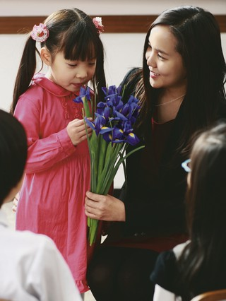 young girl looking at bouquet of flowers