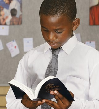young boy standing, reading from scriptures