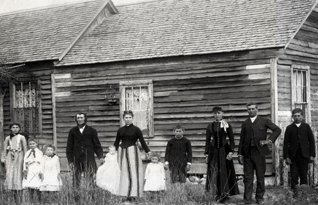 pioneer family in front of log home