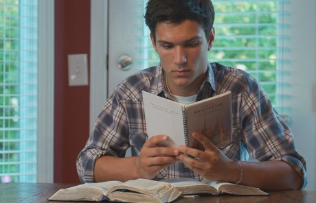 young man reading a booklet