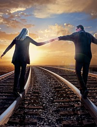 man and woman walking on train tracks