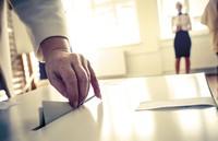 hand placing ballot in box