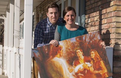 couple holding Adam and Eve painting