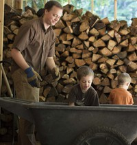 man and boys with woodpile