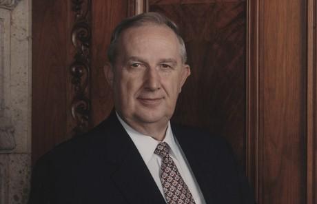 Richard G. Scott with wood panel background