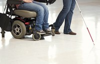feet of person in wheelchair and of blind person with cane