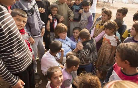 Aid worker surrounded by children in a refugee camp