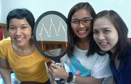 """Jóvenes tailandesas con un espejo que dice: """"Véanse en el templo""""."""
