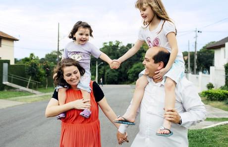 parents carrying children on shoulders