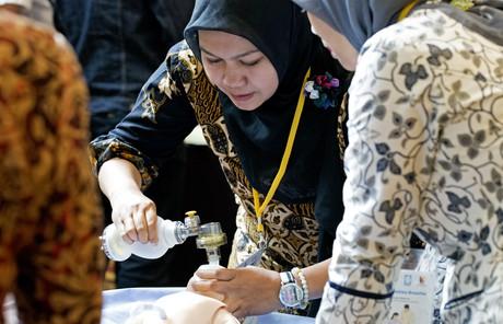 woman using neonatal resuscitation device