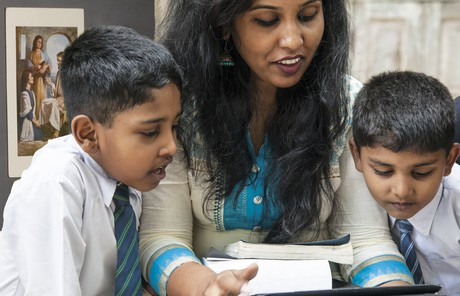 woman and two boys looking at tablet