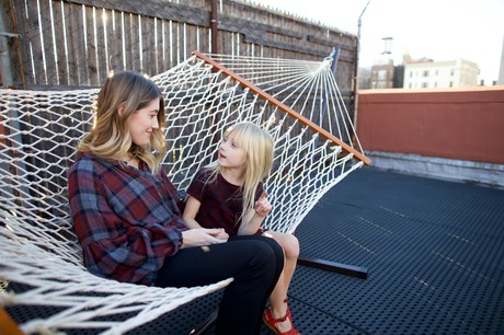 mother and daughter sitting in hammock