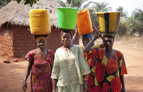 Women walking with containers on heads