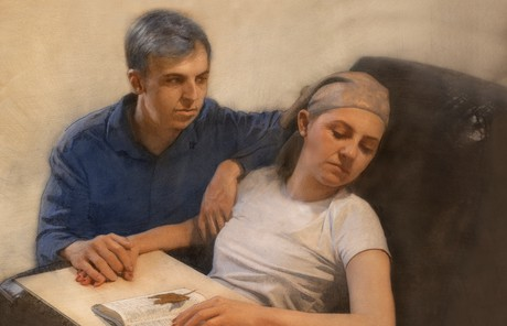man sitting next to his sleeping wife