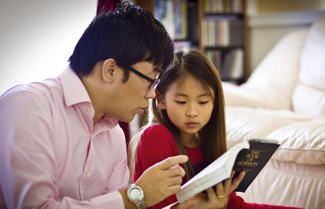 Father and daughter studying scriptures