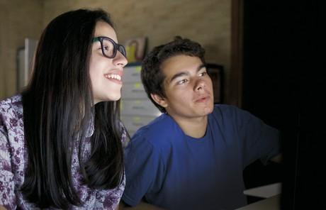 young woman and young man looking at computer screen