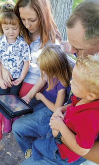 family watching general conference on a tablet