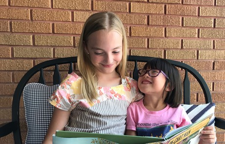 Sarah and her sister reading a book