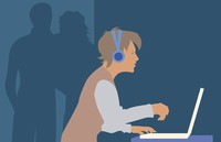 boy wearing headphones and sitting at computer