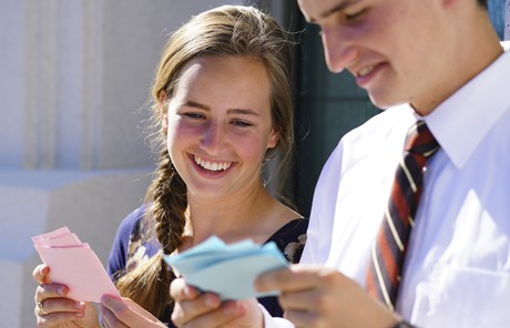 young man and young woman looking at temple name cards