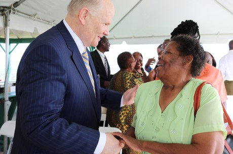 Elder Dale G. Renlund shaking hands with woman at event in Barbados