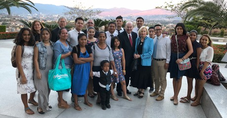 Elder Quentin L. Cook with members on temple grounds in Honduras