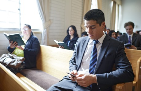youth on phone during church