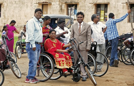 woman in India trying out hand-powered tricycle