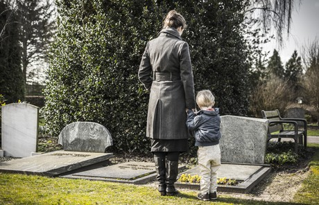 woman and boy standing in front of grave