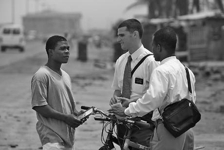 Missionaries talking to man