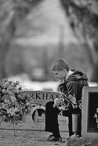 Boy with flowers at grave site