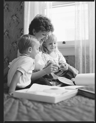A mother studying scriptures with two young children