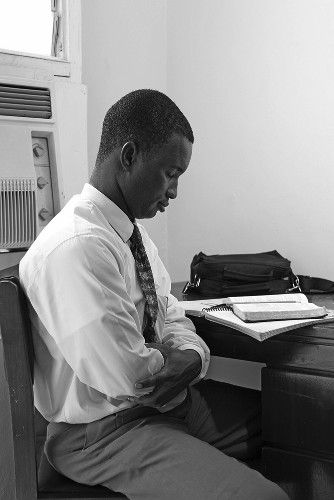 Young man praying before scripture study