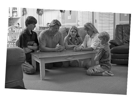 Family kneeling in prayer