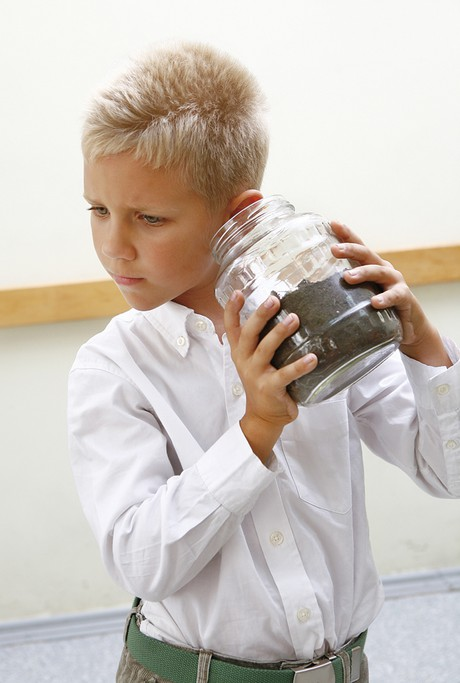 child shaking a jar filled with dirt