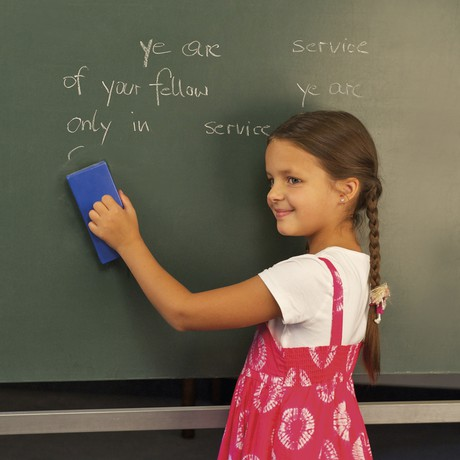 child writing on chalkboard